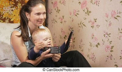 Young woman with her son sitting at home on the couch with remote control from the TV. Look at the screen attentively