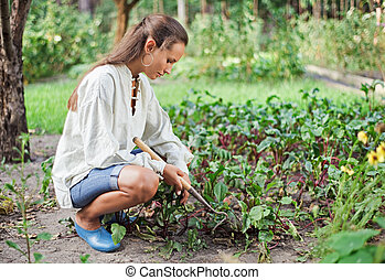Young woman with hoe working in the garden bed