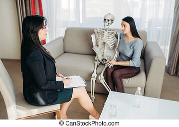 Young woman with human skeleton at psychologist