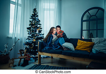 Young woman with husband looking at Christmas gift