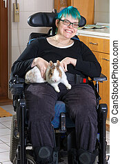 Young woman with infantile cerebral palsy due to birth complications confined to a multifunctional wheelchair caressing a pygmy rabbit as part of her therapy giving the camera a charming smile