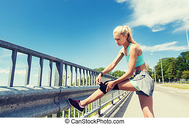 young woman with injured knee or leg outdoors