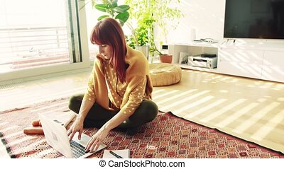 Young woman with laptop at home, sitting on the floor and working.