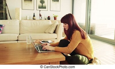 Young woman with laptop at home, working.