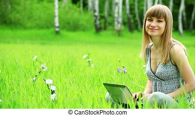 Young woman with laptop in grass