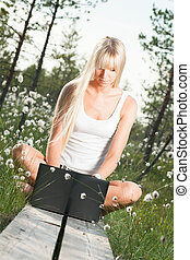 Young woman with laptop in nature