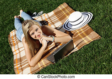 Young woman with laptop in park