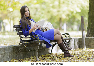 Young woman with laptop in the park
