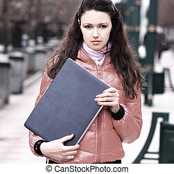 young woman with laptop on background of a winter city
