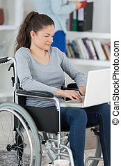 young woman with laptop on the wheelchair