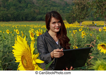 Young woman with laptop sitting on sunflower field