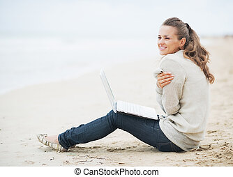 Young woman with laptop wrapping in sweater while sitting on beach