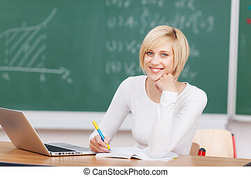 Young Woman With Laptop Writing Notes At Desk
