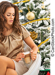 Young woman with latte macchiato near christmas tree