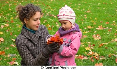 young woman with little girl gathering autumn maple leaves