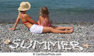 young woman with little girl lying in beach, SUMMER inscription in foreground