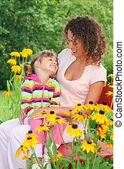young woman with little girl sitting on bench in garden