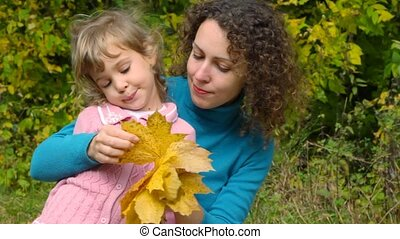 young woman with little girl take a good look at autumn leaves