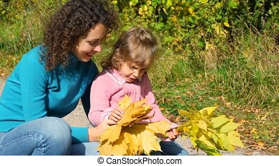 young woman with little girl take a good look at maple leaves