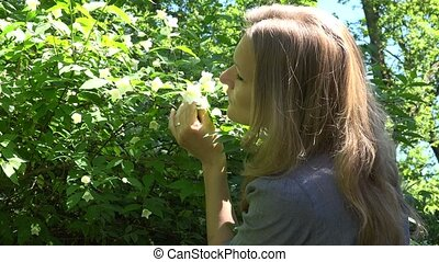 Beautiful young woman with long blond hair smelling white jasmin syringa flower blooms in garden. Static shot. 4K