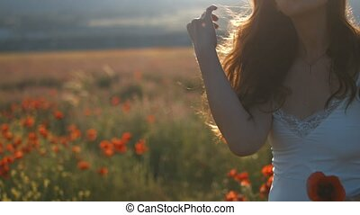 Young woman with long brunette hair walking among blooming poppy flowers