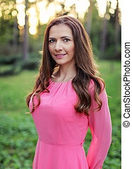 Young woman with long dark hair, wearing pink dress, photographed in spring park with nice golden sunset light.