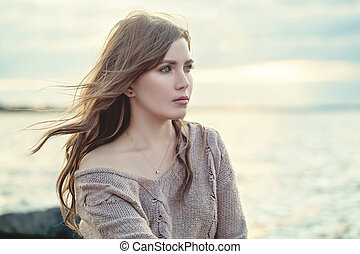 Young woman with long hair against ocean background