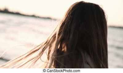 young woman with long hair dressed in a transparent tunic posing at sunset on the beach