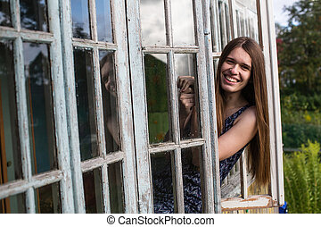 Young woman with long hair looks from of the window of veranda.