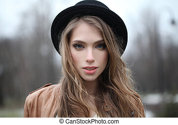 Young woman with long hair outdoors, portrait