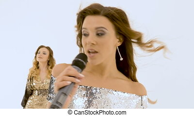 Young woman with long hair singing in studio, on white background. close-up