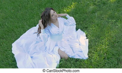 Young woman with long hair sitting on green grass. A beautiful white dress.