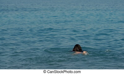 young woman with long hair swims in sea on Sunny day