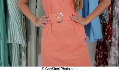 young woman with loose hair poses enjoying new peach color dress at camera near rack in shop low angle shot close view