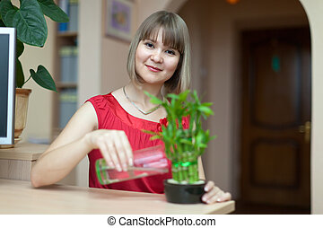 Young woman with lucky bamboo plant