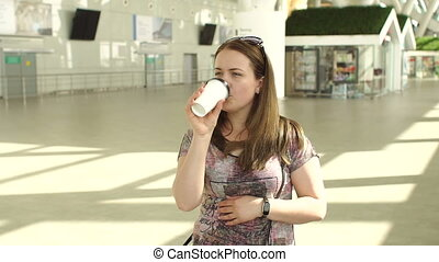 Young woman with luggage and coffee at the departure hall of the airport.