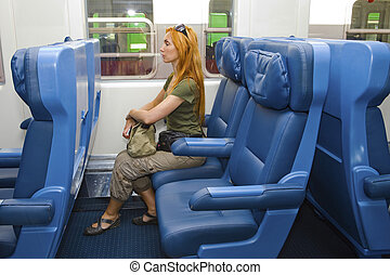 Young woman with luggage in car of train