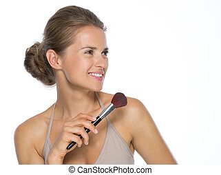 Young woman with makeup brush looking on copy space