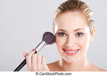 young woman with makeup brush