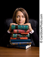 young woman with many book at the desk on black background