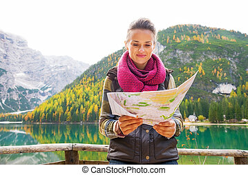 Young woman with map on lake braies in south tyrol, italy