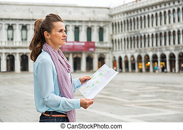 Young woman with map on piazza san marco in venice, italy