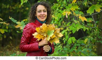 young woman with maple leaves in hands standing in autumn park