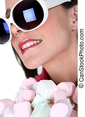 Young woman with marshmallows in hand