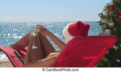 Young woman with martini glass celebrate Christmas on tropical beach
