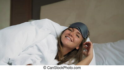 Young woman with mask lies under blanket on comfortable bed