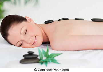 Young woman with massage stones on her back eyes closed
