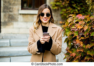 Young woman with mobile phone at autumn outdoor