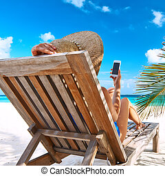 Young woman with mobile phone at the beach