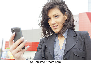 Young Woman with mobile phone, background is blured business building